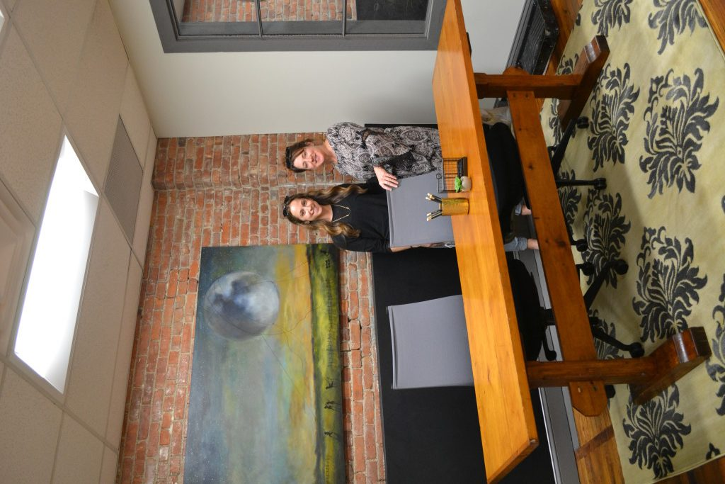 2 women on front of large wooden desk