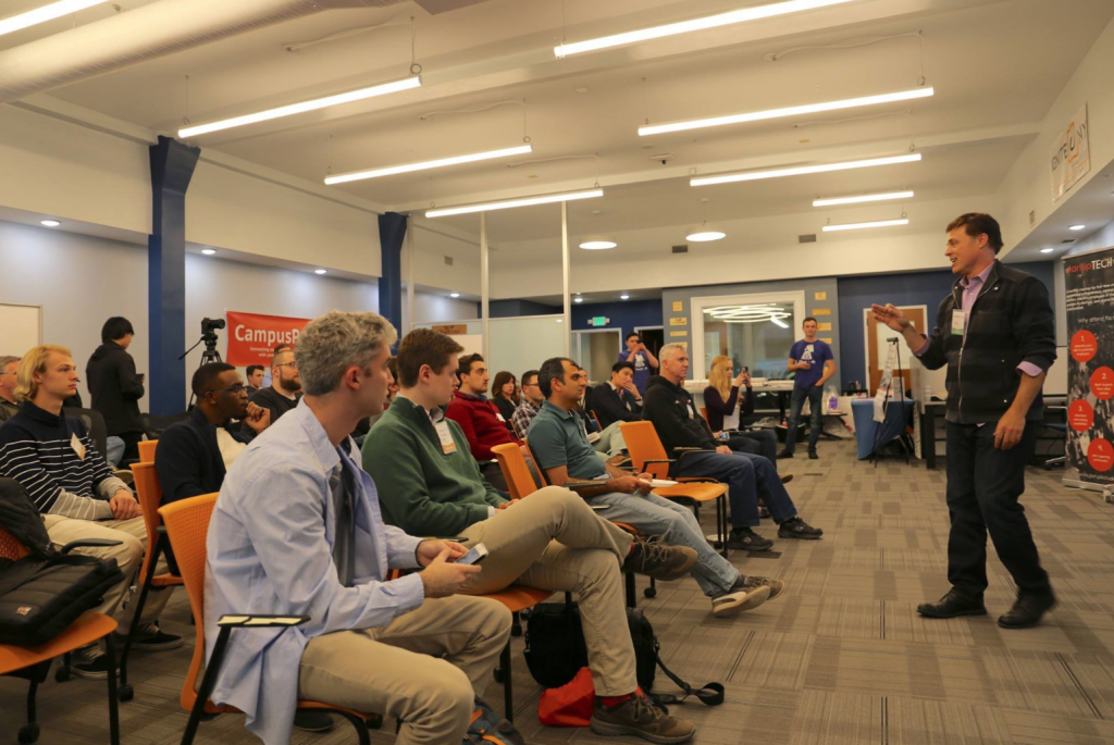 Man in front of group giving a talk
