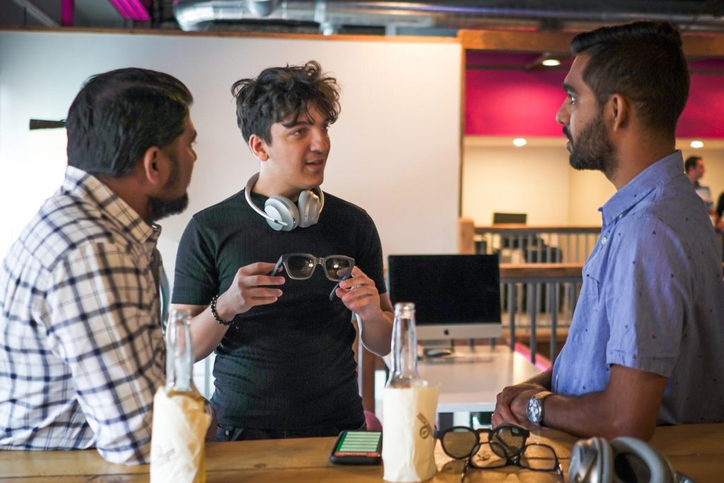 3 man standing around table talking