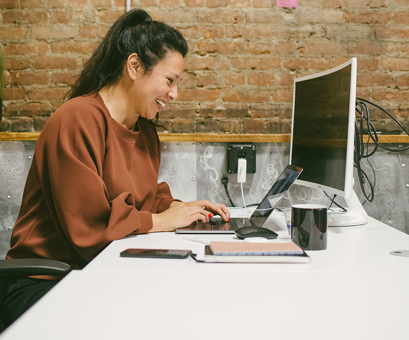 Women at desk working on laptop